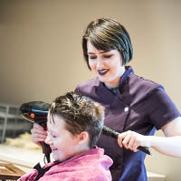 Student hairdressing smiling whilst cutting hair