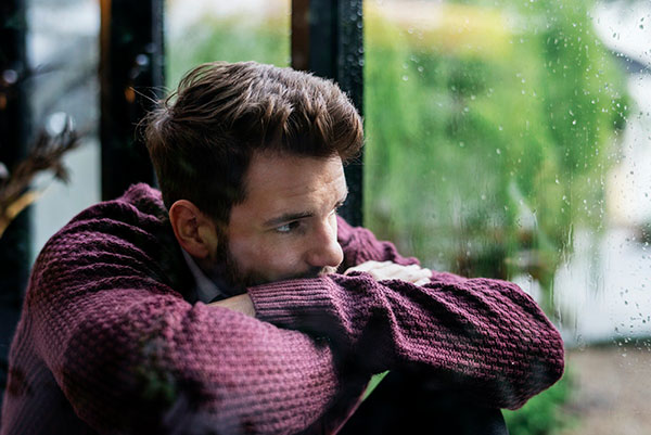 Young adult man sitting by a window looking out at the rain, leaning his head on his hands